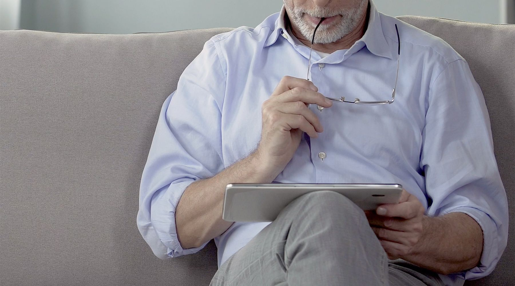 Image of a man looking at news on an iPad.