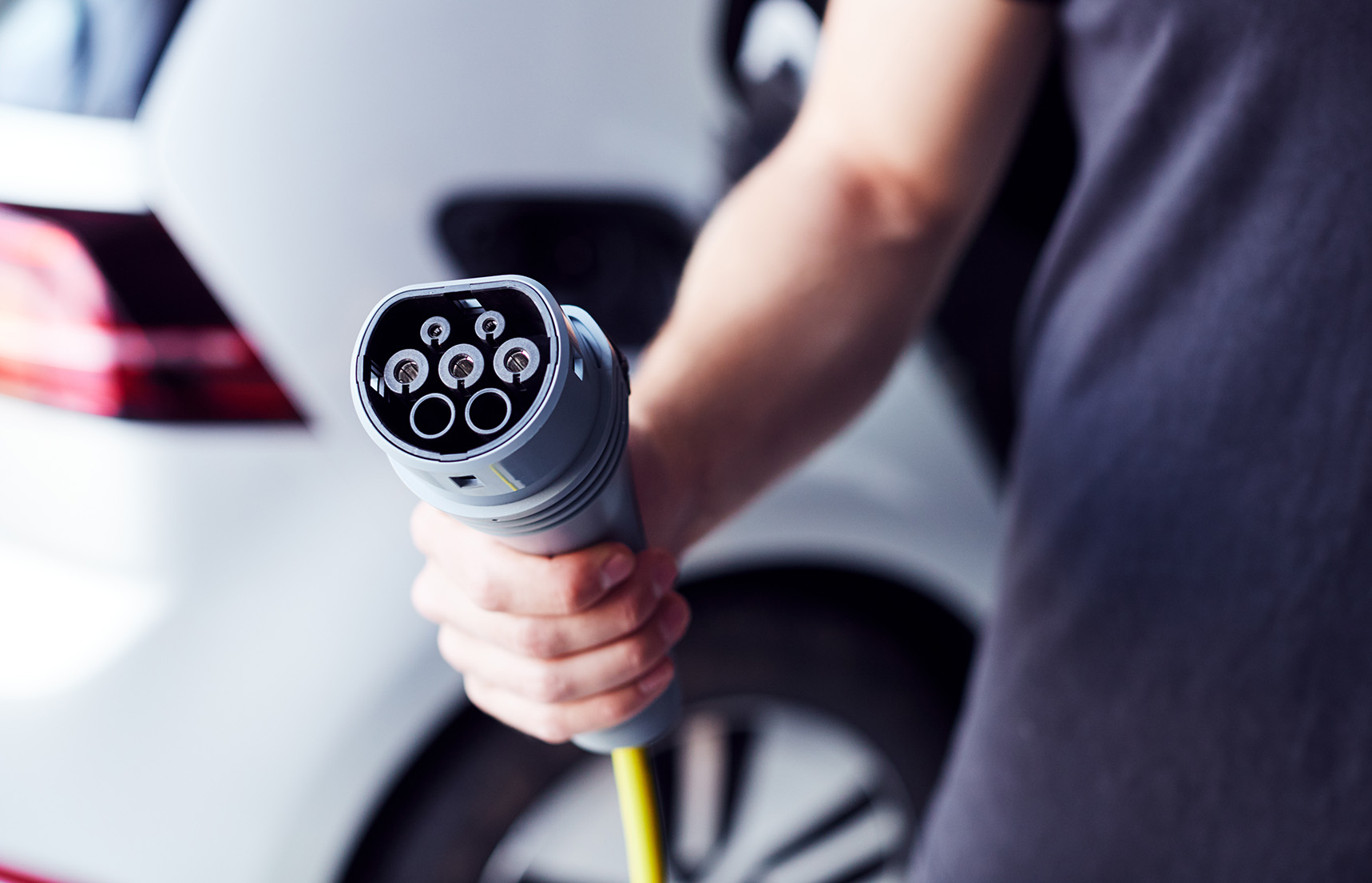 Photo of a person with electric vehicle holding an EV charging plug