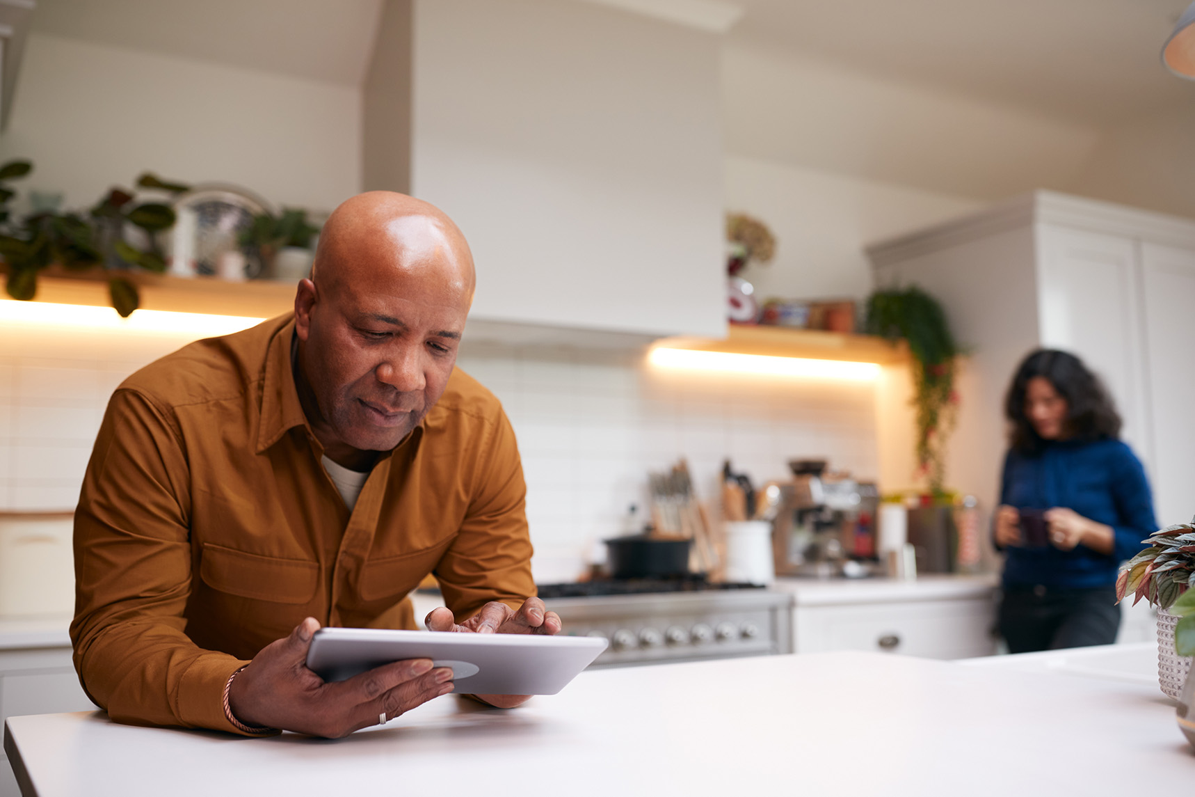 Photo of a mature man seated at a kitchen island staring at a digital tablet and a woman standing in the background looking at her phone