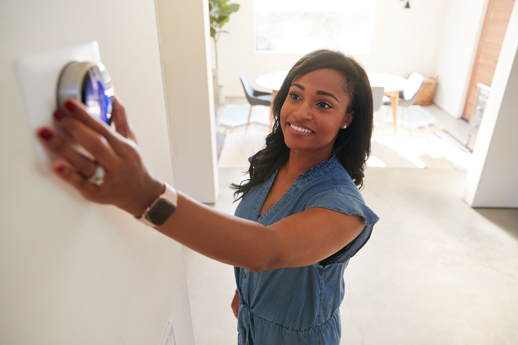Photo of a young woman adjusting a digital thermostat