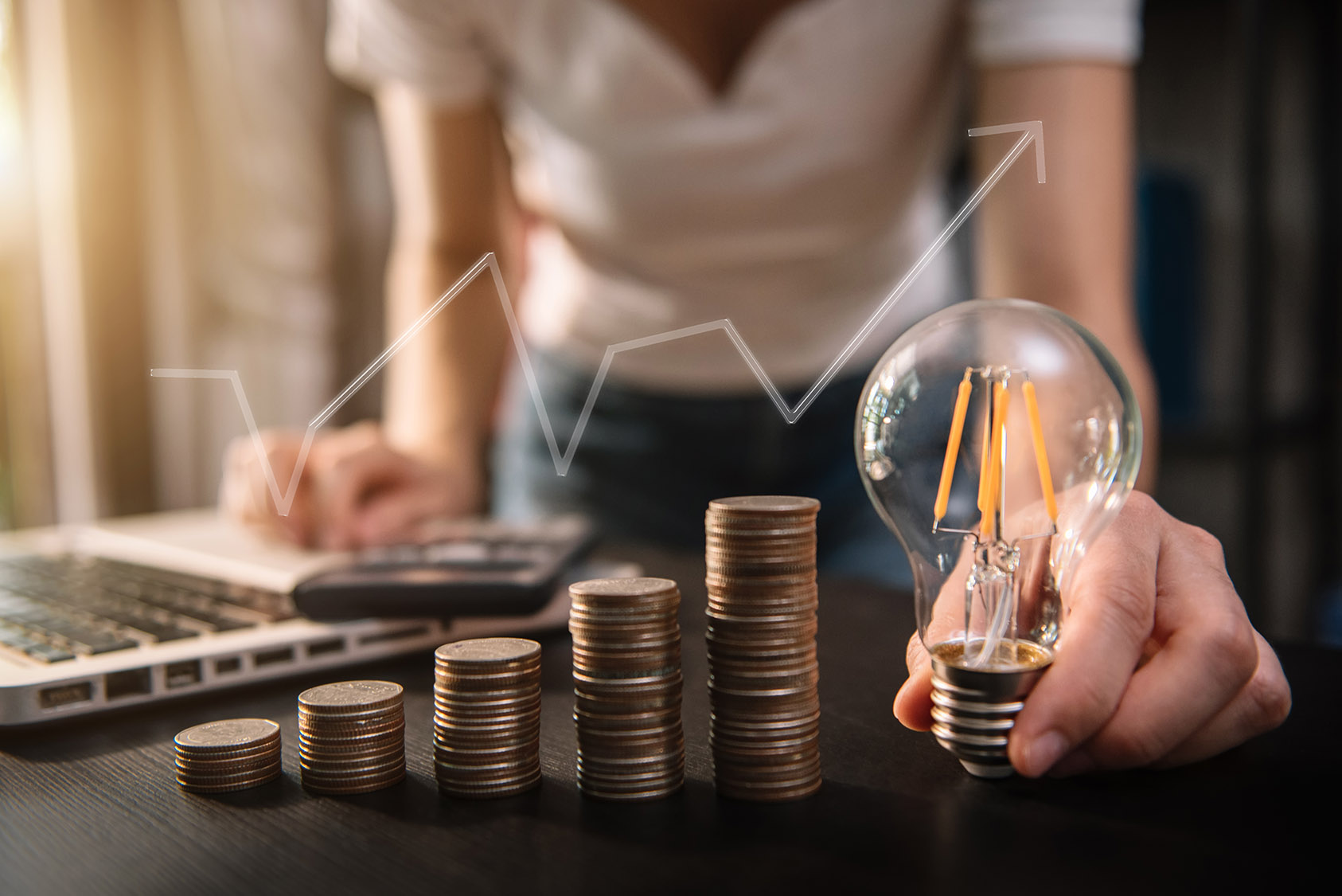 Photo of a person holding an LED lightbulb with columns of coins stacked and a laptop and calculator in the background