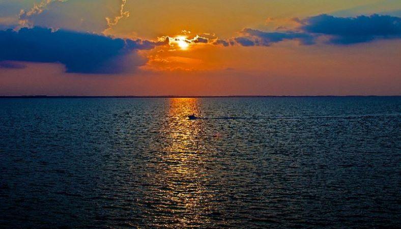 image: boat sailing on ocean at sundown