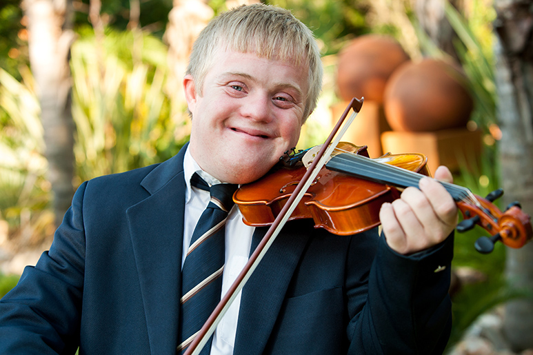 A picture of smiling teen playing a violin outside