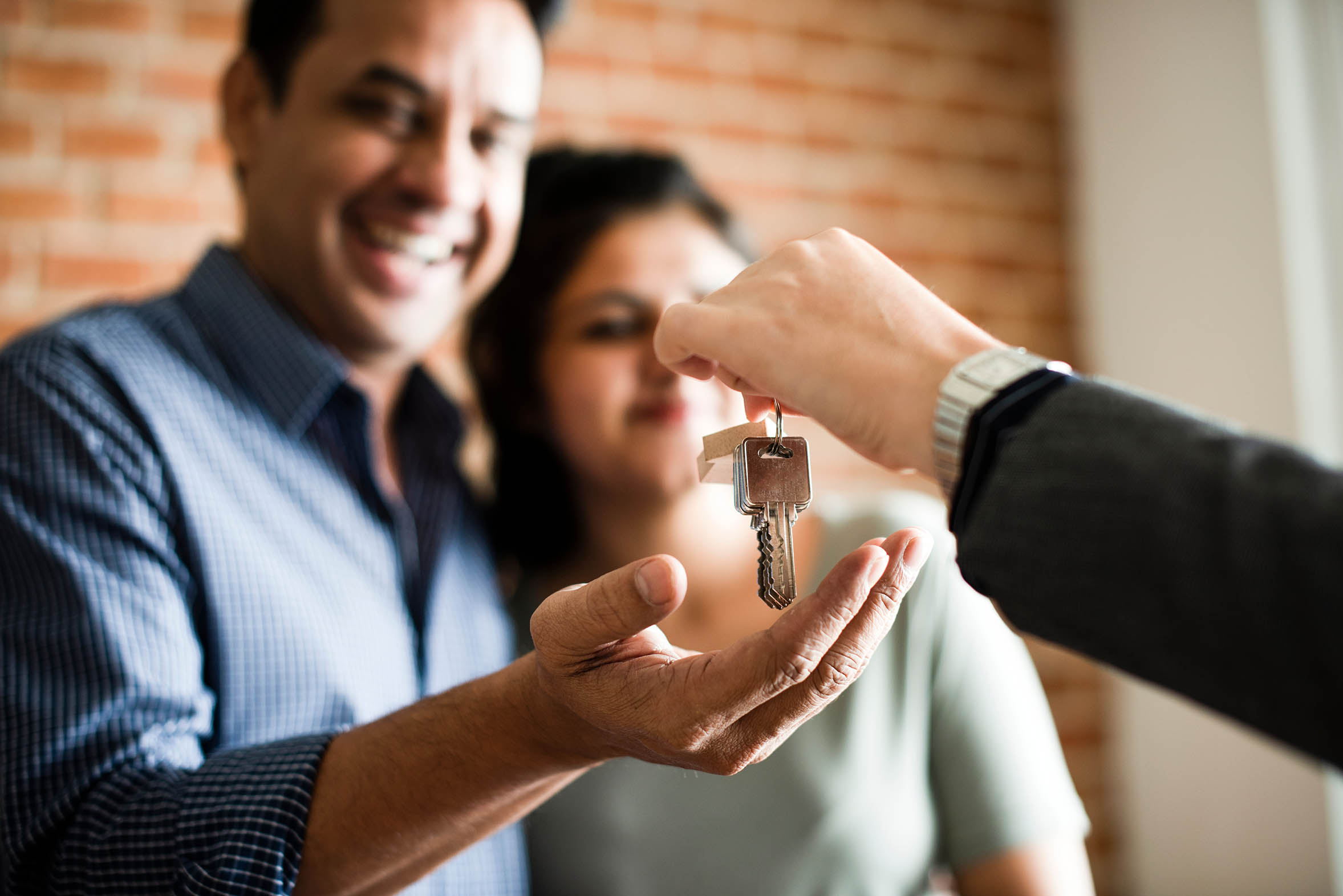 A picture of a smiling man and woman recieving keys from another person