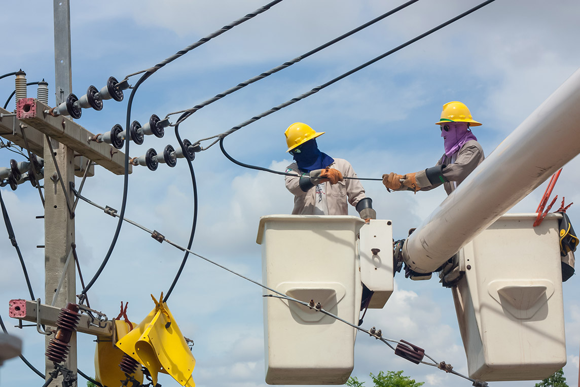 A picture of two utility workers in a work bucket working on utility lines